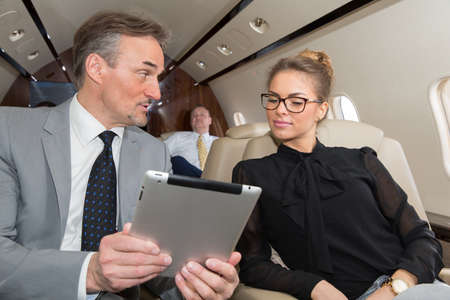 corporate jet: business team traveling in corporate jet and discussing a presentation Stock Photo