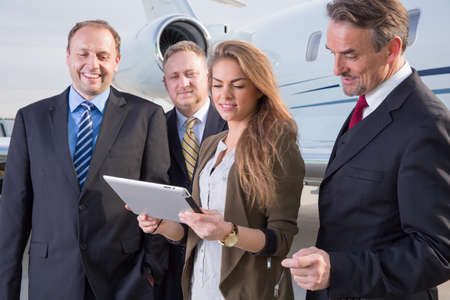 corporate jet: business team in front of corporate jet looking at tablet computer