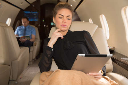corporate jet: woman in corporate jet looking at tablet computer
