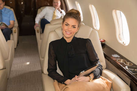 private airplane: woman in corporate jet smiling to camera