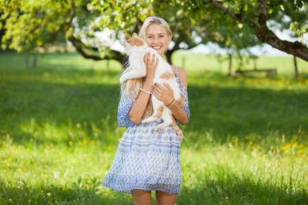 gir: Happy gir on a summer flower meadow holding a cat