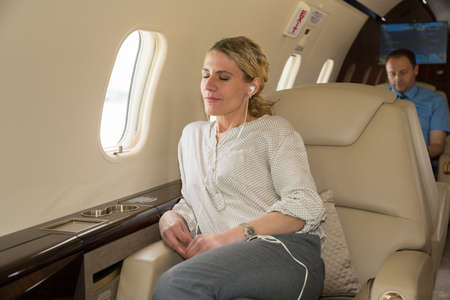 corporate jet: Business woman in a corporate jet relaxing and listening to music