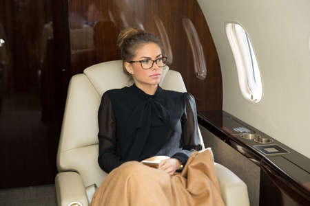 corporate jet: woman in corporate jet relaxing Stock Photo