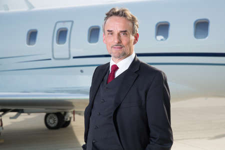 corporate jet: executive business man in front of corporate jet Stock Photo