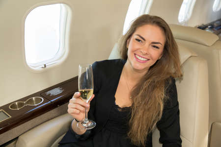 corporate jet: woman in a corporate jet drinking a glass of champagne