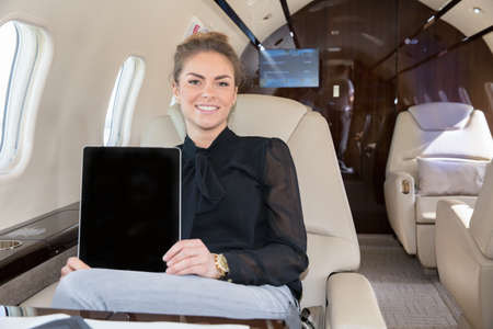 corporate jet: woman in corporate jet showing tablet computer