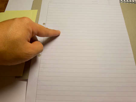 writing on paper: Finger pointing onto blank writing paper stock image