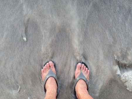 rushing: Man with flipflop on the beach with wave rushing back to the sea Stock Photo