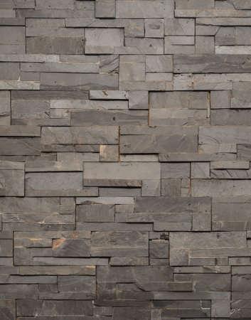 Pierre gris foncé de tuiles mur de briques de texture refait surgi