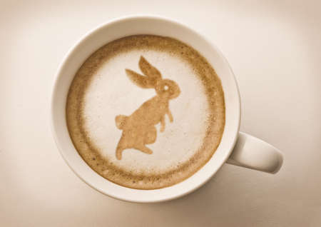 Easter rabbit drawing on latte art coffee cup photo