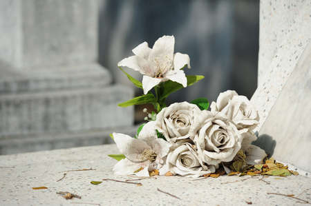 tumbas: vieja flor blanca en la tumba falsa Foto de archivo