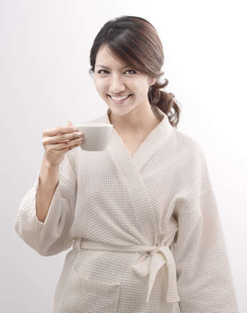 asian woman in bathrobe with coffee cup on white background photo