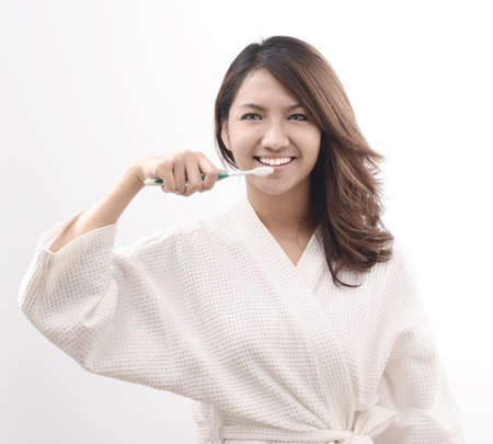 asian woman with toothbrush in bathrobe morning mood photo