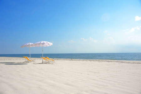 sea, tropical beach with umbrella and chairs photo
