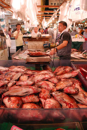 TOKYO - JULY 17   Fish seller at Tsukiji Market, the biggest wholesale market in Japan, market will be moved to new location in 2014, July 17, 2008 in Tokyo, Japan  Stock Photo - 18329389