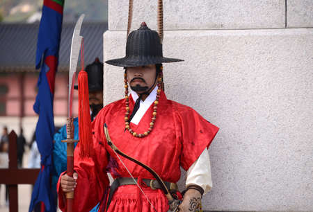 SEOUL, KOREA - OCTOBER 22 : Korean guard dressed in a red uniform and holding a lance stands at the entrance to the Gyeongbokgung Palace in Seoul, Korea on October 22, 2014.
