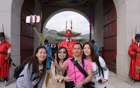tourist spot: SEOUL, KOREA - OCTOBER 22 : Tourists selfie with mobile phone in front of Gyeongbokgung Palace in Seoul, Korea