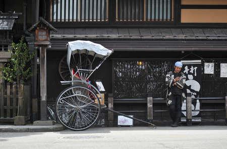 TAKAYAMA, JAPAN - APRIL 12 : Japanese cart with driver in front of a shop in Takayama taken April 12, 2010.