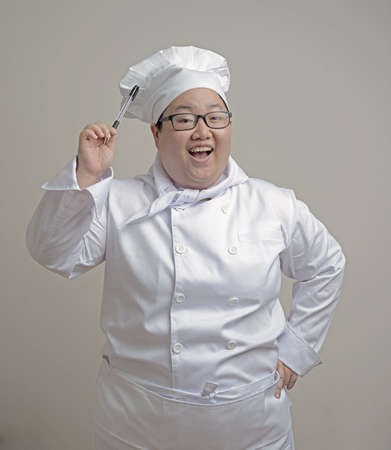 Asian lady fat chef with a pen on plain background Stock Photo