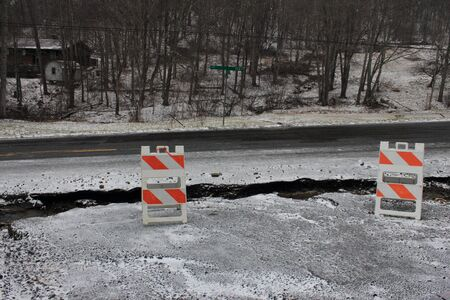 washed out: A road was washed out in a flood, then dusted with snow  Stock Photo