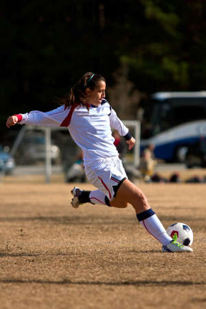 Female Soccer Player Winds Up To Kick Ball in Game photo