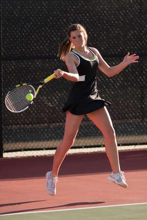 hits: Female Tennis Player Hits Powerful Forehand Stock Photo