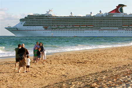 Fort Lauderdale, FL, USA - December 28:  A family poses for a photo on the Ft. Lauderdale beach as a cruise ship in the background heads out to sea.