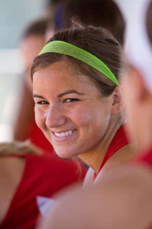 Female Softball Player Smiles Inside Dugout