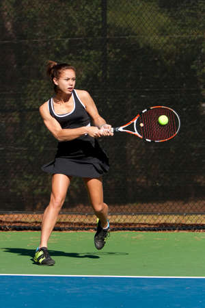 Female High School Tennis Player Hits Backhand photo