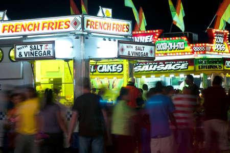 People Walk Amid Fast Food Vendors At County Fair