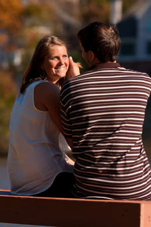 caresses: A young man gently caresses the smiling, sunlit face of his girlfriend while sitting on a bench.