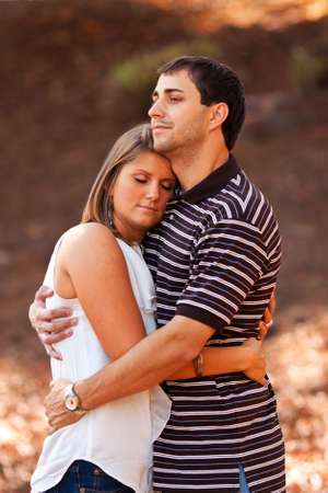 hugging couple: A young couple very much in love share a sweet embrace.