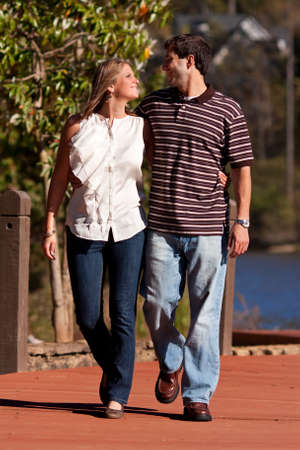 walk in: A young couple in love walk arm in arm along a dock by a lake.
