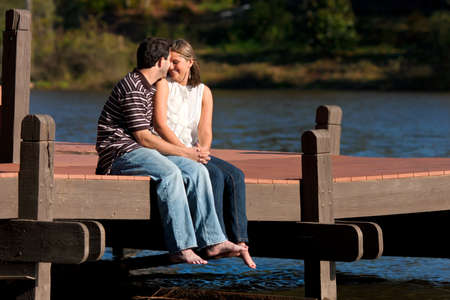 A young couple in love share an intimate moment while sitting barefoot on a dock over a lake.