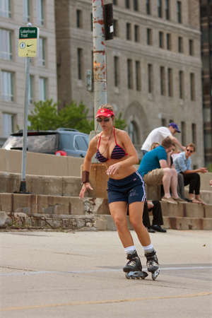lake shore drive: Chicago, IL, USA - May 26, 2012:  An athletic woman rollerblades through an asphalt area that separates Chicagos Lake Shore Drive from Lake Michigan.  The warm weather and Memorial Day holiday brought thousands outdoors to kickoff summer.