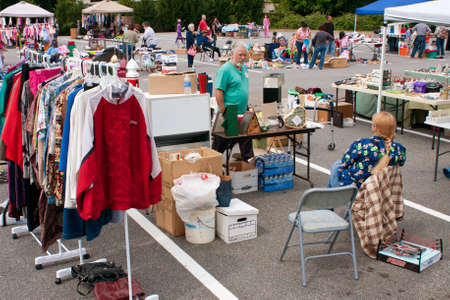 garage sale: Lilburn, GA, USA - April 21:  Shoppers look over merchandise on display at the Lilburn citywide garage sale, held in the city hall parking lot.