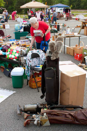 Lilburn, GA, USA - April 21:  An elderly woman looks over merchandise on display at the Lilburn citywide garage sale, held in the city hall parking lot. Redactioneel