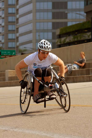 paralyzed: CHICAGO, IL - MAY 26:  An unidentified female in a racing wheelchair works out on an asphalt recreational area that runs alongside Chicagos famous Lakeshore Drive.  The warm weather brought many locals and tourists outside to enjoy the long Memorial Day
