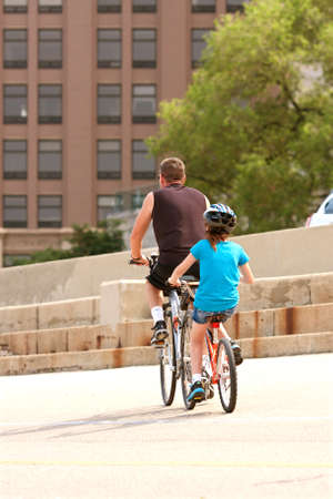 lake shore drive: CHICAGO, IL - MAY 26:  An unidentified man and girl ride a tandem bicycle through an asphalt recreational area just off Chicagos Lake Shore Drive.  The Memorial Day holiday weekend brought many people outdoors to kickoff summer.