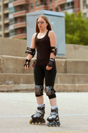 lake shore drive: CHICAGO, IL, USA - MAY 26, 2012:  A woman wearing elbow and knee pads rollerbaldes through an asphalt area that separates Chicagos Lake Shore Drive from Lake Michigan.  The warm weather and Memorial Day holiday brought thousands outdoors to kickoff summe