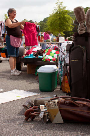 Lilburn, GA, USA - April 21:  A senior woman prepares merchandise for sale at her table at the Lilburn citywide garage sale, held in the city hall parking lot.