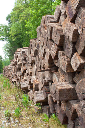 wood railroad: A stack of wood railroad ties is piled high beside a railroad track and stretches out into the horizon.  Editorial