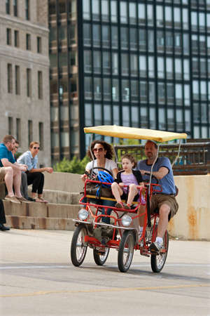 CHICAGO, IL - MAY 26:  An unidentifed family pedals a four-wheeled bike along a concrete strip between Chicago's Lakeshore Drive and Lake Michigan.  Thousands of tourists were in town to kickoff summer with the long Memorial Day holiday weekend.  Stock Photo - 15056002