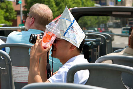 Chicago, IL, USA - May 26, 2012:  An unidentified male tourist, wearing a map for a paper hat, takes photos of Chicago from on top of a double-decker sightseeing bus.  The Memorial Day weekend brought many locals and tourists outdoors to kickoff summer.