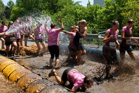 Atlanta, GA , USA - April 28:  A group of unidentified women competing in the Dirty Girl Mud Run, splash through the mud pit and get drenched with a fire hose as they near the finish line of the women only obstacle course race.