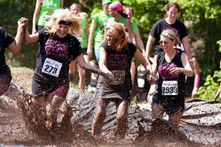 muddy clothes: Atlanta, GA , USA - April 28:  A group of unidentified women competing in the Dirty Girl Mud Run, splash through the mud pit as they near the finish line of the women only obstacle course race. Editorial