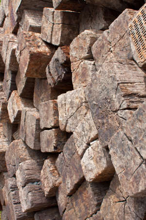 Wood texture of large stack of railroad ties piled high next to railroad tracks.
