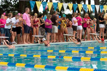 backstroke: Lawrenceville, GA, USA - June 14:  Female youth swimmers get in ready position to start backstroke race  during a neighborhood swim meet between three swim teams.