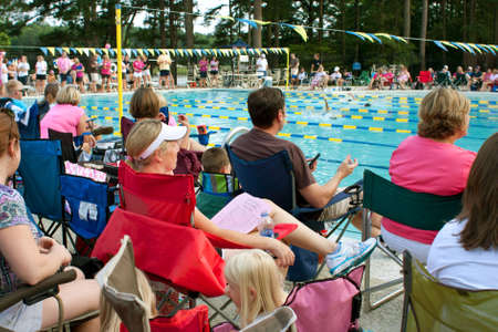 Lawrenceville, GA, USA - June 14:  Parents and spectators sit poolside to watch a neighborhood swim meet between three swim teams.
