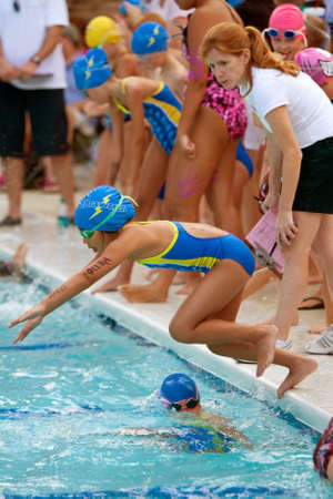 Lawrenceville, GA, USA - June 14:  A female youth swimmer dives into pool to swim her leg of a relay race during a neighborhood swim meet between three swim teams.